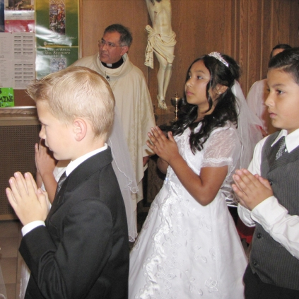 First Communicants wait at the entrance of the church