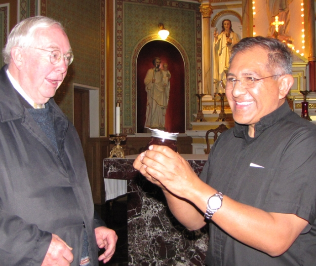 Monsignor accepting a gift of jam from tour leader Dennis Gallagher